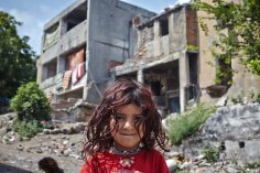 5/ Aysha, 5, stands outside the unfinished, abandoned building in Istanbul that has been her home for half a year. She lives here with her mother and 10 siblings. The majority of Syrian refugees live in urban settings, often sharing overcrowded apartments or abandoned buildings. / UNHCR / Shawn Baldwin