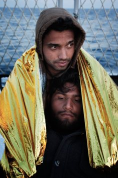 Italy / Mediterranean Sea / Two people rescued by the Italian Navy's humanitarian operation share a thermal blanket on the deck of the Verga, the ship that will take them to the mainland. UNHCR / A. D'Amato / March 2014 Every year tens of thousands of people risk their lives by crossing the Mediterranean on overcrowded and often unseaworthy boats in a bid to reach Europe. Many are fleeing violence and persecution and are in need of international protection. Thousands die every year trying to make it to places like Malta or Italy's tiny Lampedusa Island. It took the loss of some 600 people in boat sinkings last October to focus world attention on this humanitarian tragedy. Italy has since launched a rescue-at-sea operation using naval vessels, which have saved more than 10,000 people. Photographer Alfredo D'Amato, working with UNHCR, was on board the San Giusto, flagship of the Italian rescue flotilla, when rescued people were transferred to safety. His striking images follow. *** Local Caption *** The identities of the people in the photos must be protected.DO NOT PUBLISH NAMES OR PERSONAL STORIES OF THE PEOPLE IN THE IMAGES.