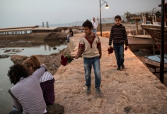"Lebanon/ Syrian refugees/ Manhal, aged nine, and Ahmed, 11, brothers from the northern Syrian city of Aleppo, sell flowers by the sea in Byblos. They go to school by day, and work all evening. Their older brother doesn't go to school at all. ""I would if I could,"" says Mohammed. ""But who would help my father with the rent?""/ UNHCR/ Lynsey Addario/ March 2014)"